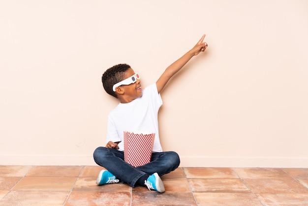 Chico afroamericano sosteniendo palomitas y apuntando hacia arriba