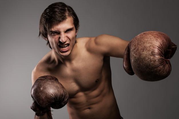 Chico agresivo en guantes de boxeo