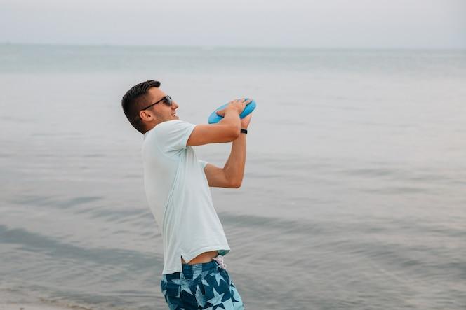 Chico alegre a punto de lanzar un disco frisbee, jugando cerca del mar.