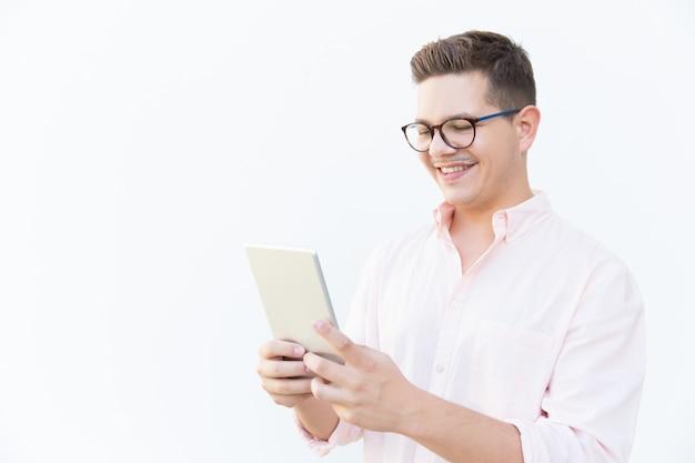 Chico alegre en anteojos viendo contenido en tableta