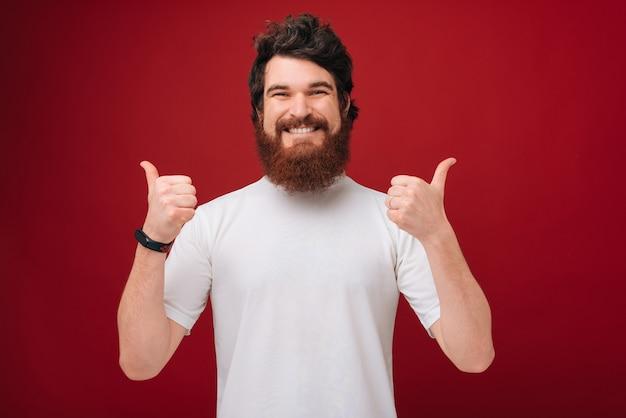 Chico alegre con barba mostrando los pulgares hacia arriba sobre la pared roja
