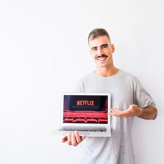 Chico alegre demostrando portátil con el sitio de netflix