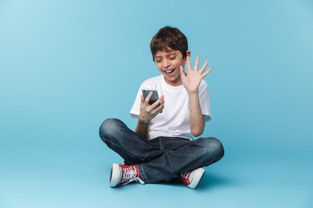 De chico alegre europeo con pecas vistiendo camiseta blanca casual sosteniendo y usando el teléfono inteligente mientras está sentado en el piso aislado sobre la pared azul