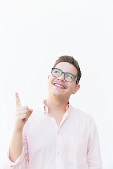 Chico alegre feliz en gafas mirando y apuntando con el dedo hacia arriba
