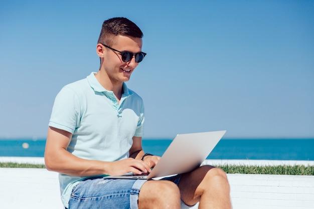 Chico alegre en gafas de sol trabajando en la computadora portátil, escribiendo, navegando por sitios web