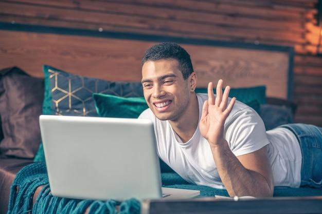 Chico alegre guapo saludando en línea frente a la pantalla de una computadora portátil, acostado en su cama apoyado en los codos.