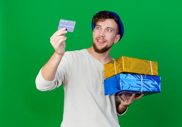 Chico alegre joven guapo partido eslavo con sombrero de fiesta sosteniendo cajas de regalo y tarjeta de crédito mirando la tarjeta aislada en la pared verde