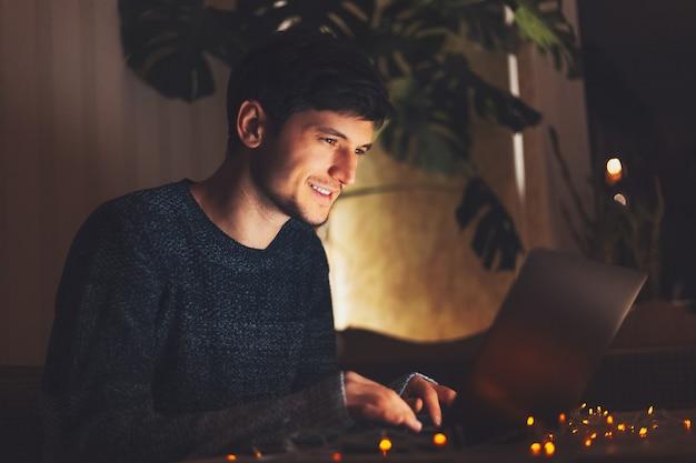 Chico alegre joven de noche trabajando en equipo portátil en una habitación oscura con guirnaldas en la mesa en casa.