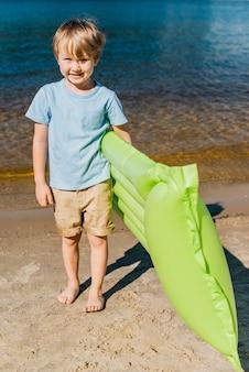 Chico alegre lindo con colchón inflable en la playa