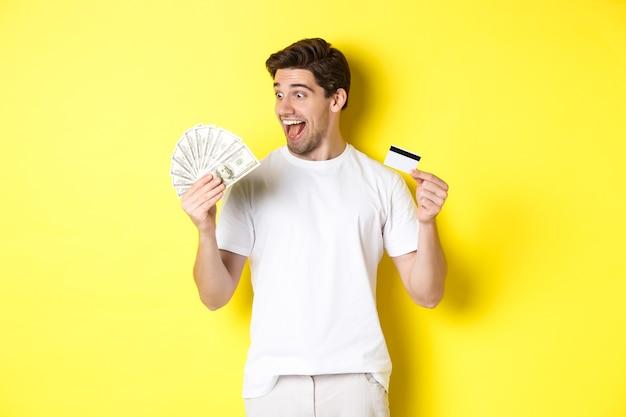 Chico alegre mirando dinero, con tarjeta de crédito, concepto de crédito bancario y préstamos, de pie sobre fondo amarillo.