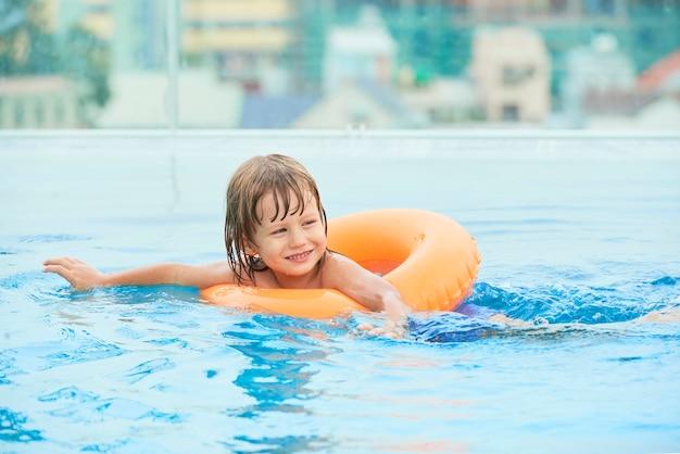 Chico alegre nadando en la piscina