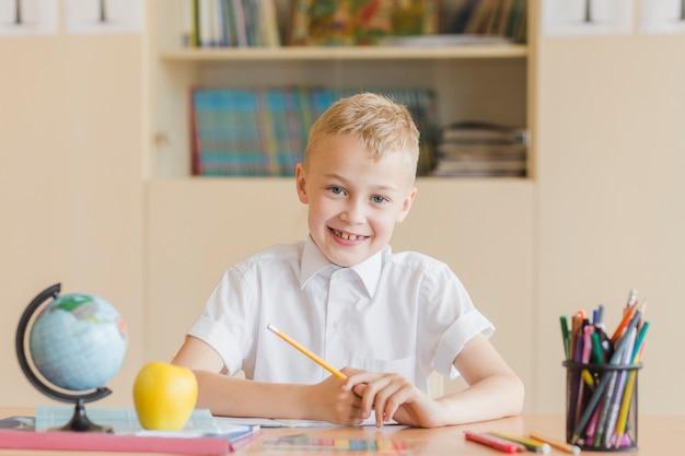 Chico alegre sentado en el escritorio de la escuela