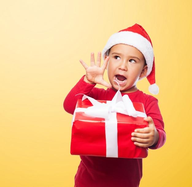 Chico alegre sujetando un regalo rojo