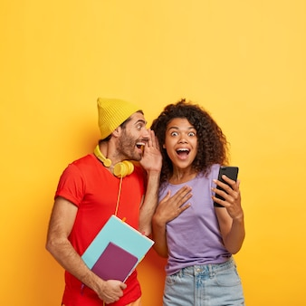 Un chico alegre le susurra un secreto a su novia, comparte chismes, diviértete después de las clases. la excitada mujer de cabello rizado sostiene el teléfono celular y recibe información interesante de su compañero de grupo. dos estudiantes discuten algo