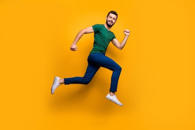Chico alegre de tamaño completo saltar correr rápido sobre la pared de color amarillo