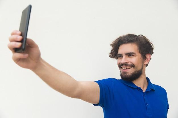 Chico alegre tomando selfie en teléfono móvil