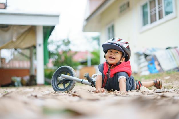 Un chico asiático de unos 2 años anda en bicicleta de equilibrio para bebés y cae.