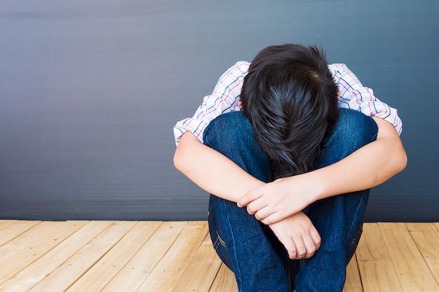 Un chico asiático de 7 años se siente triste.