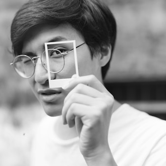 Chico asiático asomando a través de un marco de fotos