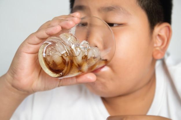Chico asiático bebiendo refrescos