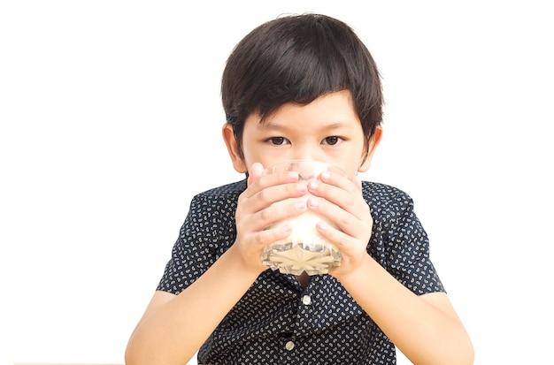Chico asiático está bebiendo un vaso de leche sobre fondo blanco