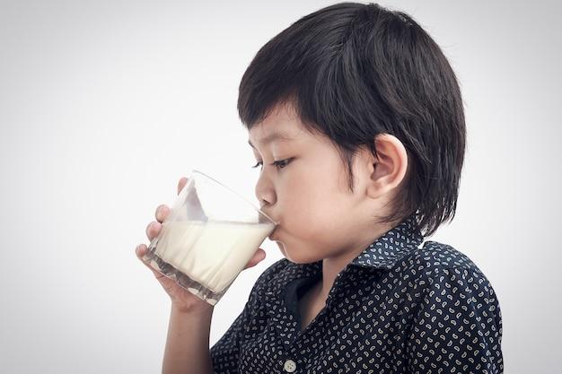 Chico asiático está bebiendo un vaso de leche