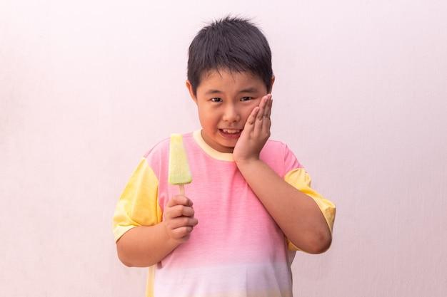 Chico asiático comiendo un retrato de paleta