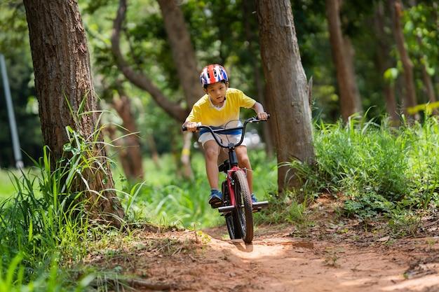 Chico asiático está entrenando para un feliz ciclismo de montaña.