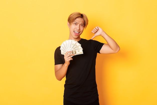 Chico asiático guapo descarado señalando con el dedo en efectivo y mirando complacido. hombre coreano pidió prestado dinero, pared amarilla permanente