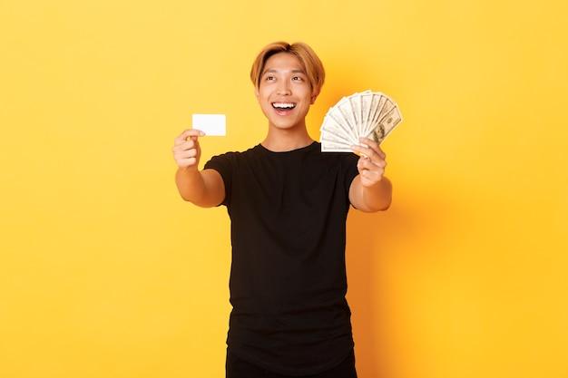 Chico asiático guapo feliz que mira la esquina superior izquierda pensativa y complacida mientras muestra dinero y tarjeta de crédito, pared amarilla