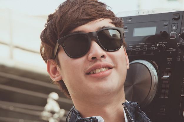 Chico asiático guapo con giradiscos dj mezclador