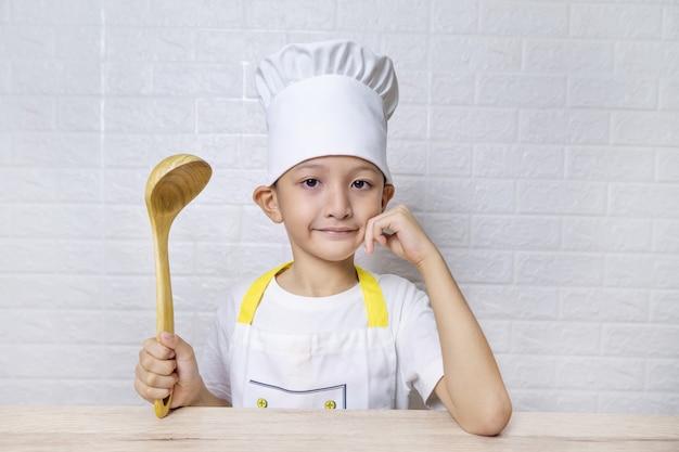 Chico asiático lindo con delantal y gorro de cocinero en la pared de ladrillo blanco.