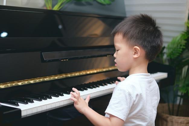 Chico asiático lindo tocando el piano