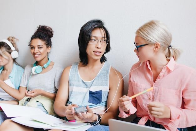 Chico asiático con pelo largo discutiendo sobre la nueva canción con una amiga rubia en gafas mientras una mujer negra sonriendo retrato interior de estudiantes disfrutando de la música y bromeando.