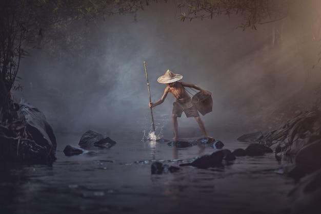 Chico asiático pescando en el arroyo, campo de tailandia