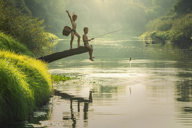 Chico asiático pescando en el río