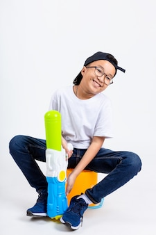 Chico asiático con pistola de agua en el fondo blanco