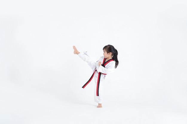 Chico asiático taekwondo pateando en estudio blanco