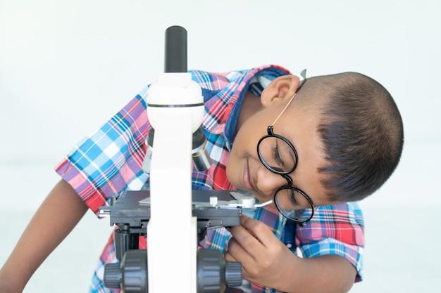 Chico asiático usa microscopio en laboratorio para investigación