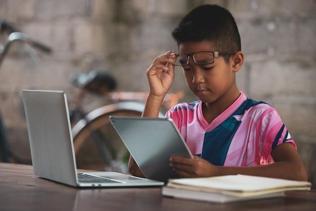 Chico asiático usando la computadora portátil en la mesa, vuelve a la escuela