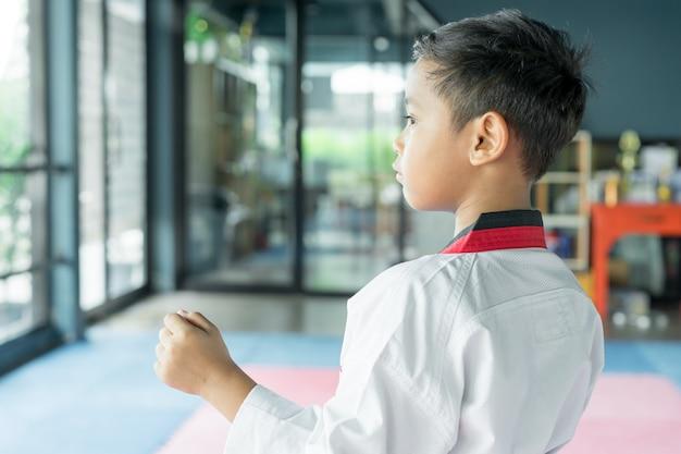 Chico asiático vestido con traje blanco de taekwondo que actúa listo para la batalla, concepto deportivo