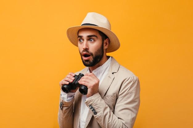 Chico asombrado con sombrero sosteniendo binoculares en pared naranja