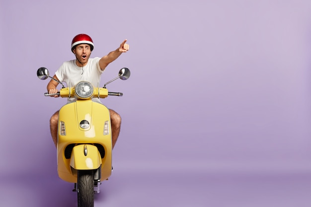 Chico asustado con casco conduciendo scooter amarillo