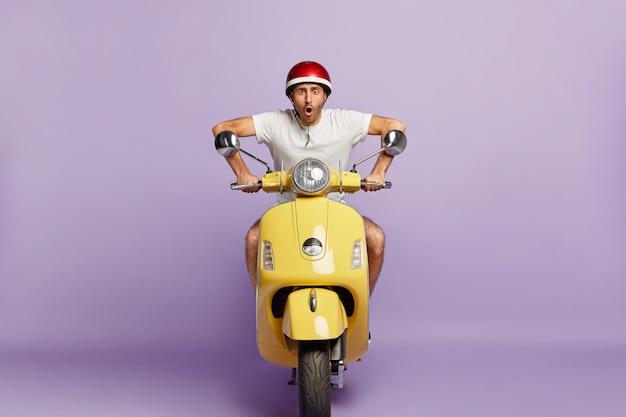 Chico aterrorizado con casco conduciendo scooter amarillo