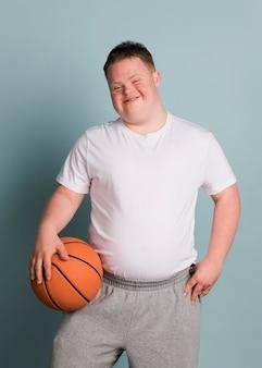 Chico atlético lindo con síndrome de down sosteniendo una pelota de baloncesto