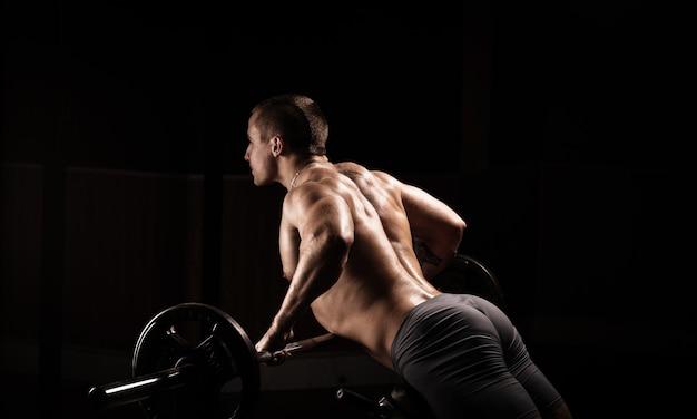 Chico atlético muy poderoso, ejecuta ejercicio con mancuernas, en el pabellón de deportes