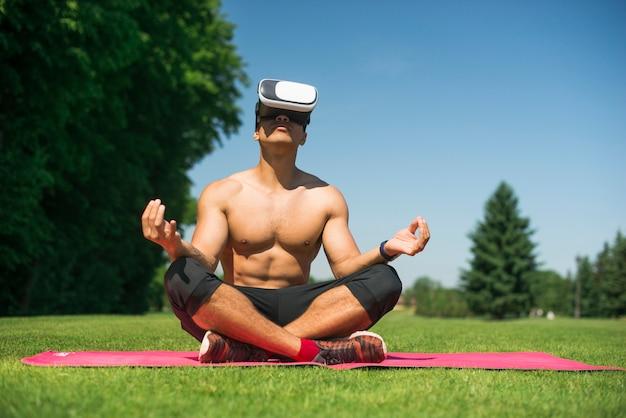 Chico atlético usando unas gafas de realidad virtual al aire libre