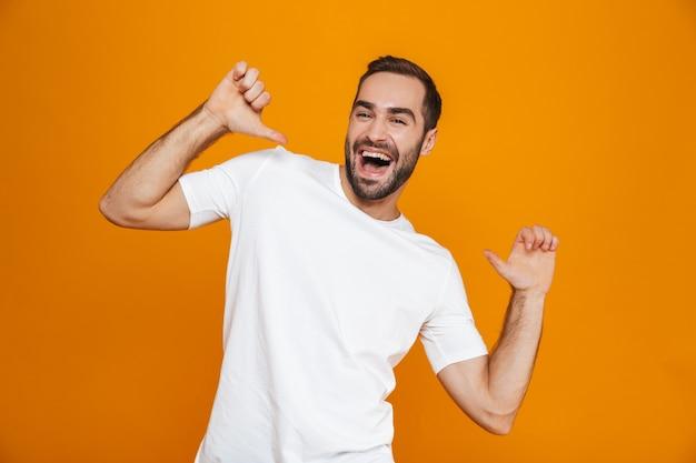 Chico atractivo en camiseta apuntando con el dedo a sí mismo mientras está de pie, aislado en amarillo