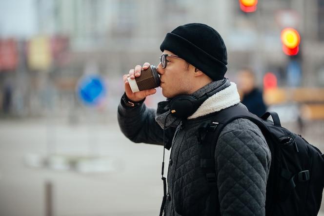 Chico atractivo en anteojos bebiendo café, al aire libre. vestido con chaqueta y sombrero