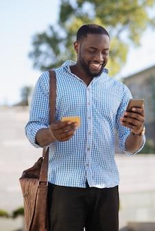 Chico atractivo expresivo alegre de pie en la calle y hacer un pedido usando una aplicación especial y pagando con su tarjeta de crédito